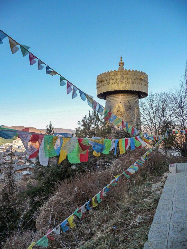 Essere un turista sostenibile - Yunnan tempio tibetano con bandierine tibeetane tra i monti di Shangrila