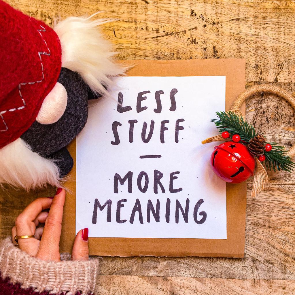 """scritta """"Less stuff, more meaning"""" con oggetti natalizi su base di legno"""