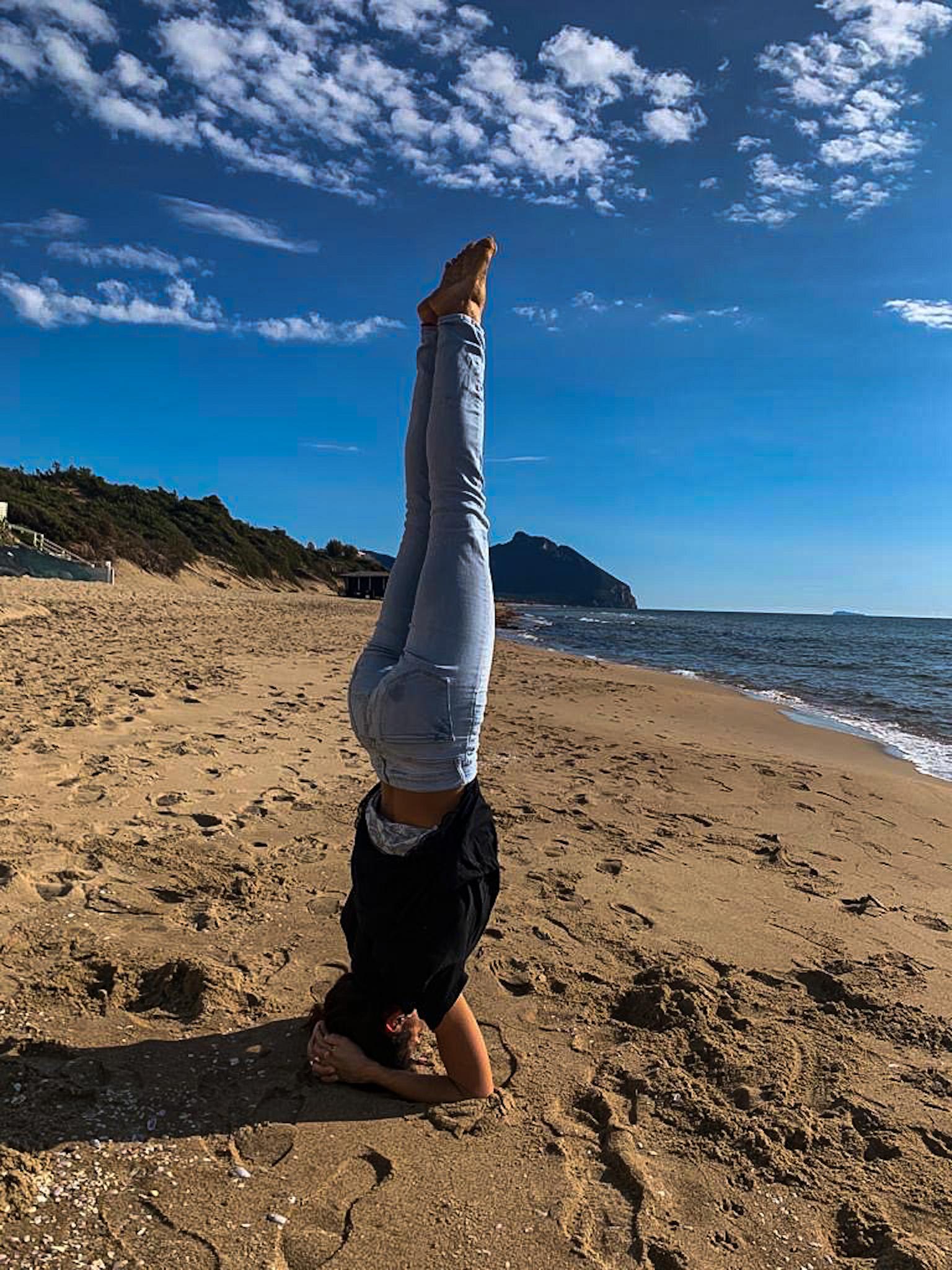 posizione di yoga a testa in giù in riva al mare