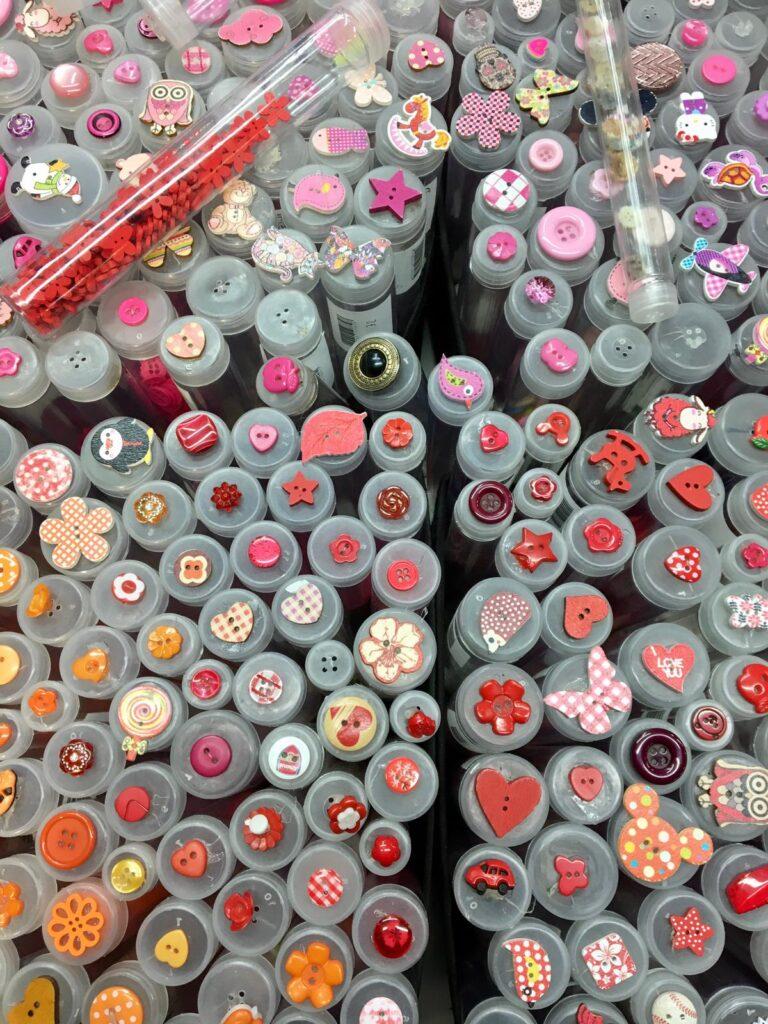 Tubicini di bottoni di tanti colori in una bancarella del mercato Trionfale di Roma