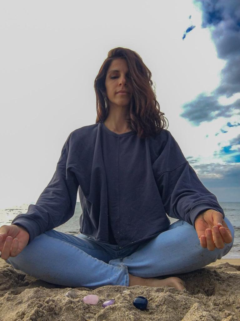 ragazza che medita a gambe incrociate su una spiaggia