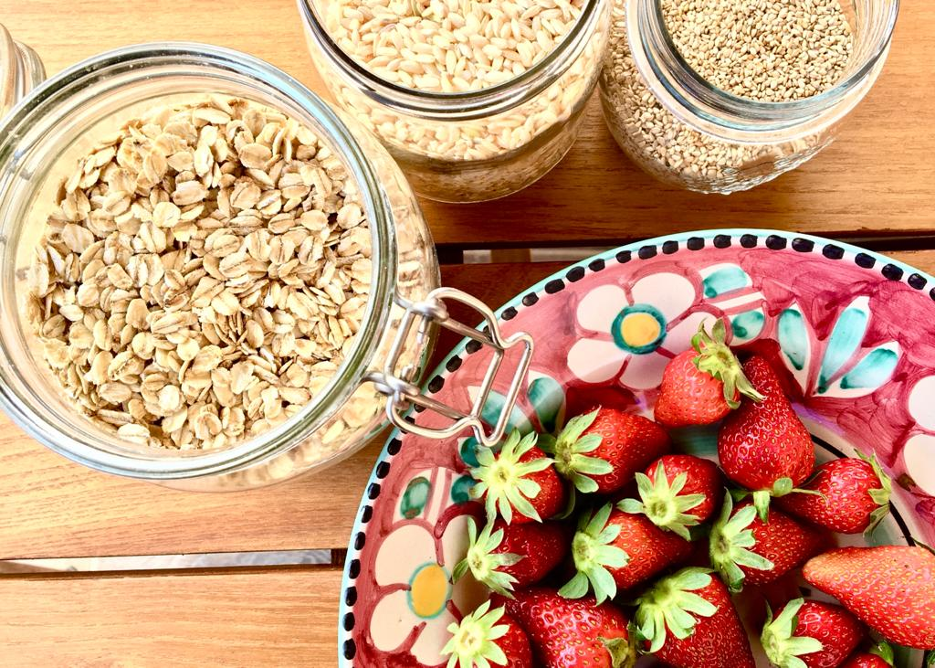 piatto di fragole e vasi di cereali su tavolo in legno