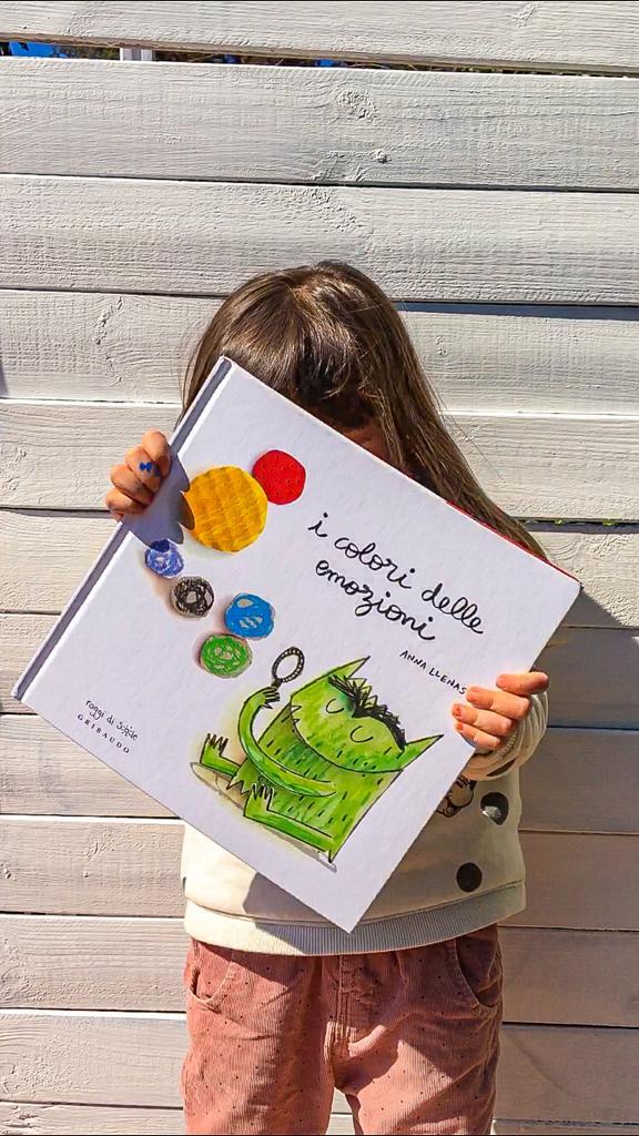 bambina che mostra un libro per bambini sulle emozioni coprendosi il volto con esso