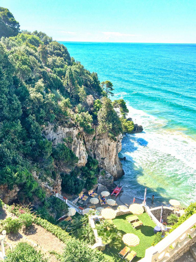 baia privata con acqua cristallina e roccia a strapiombo ricoperta di vegetazione verde