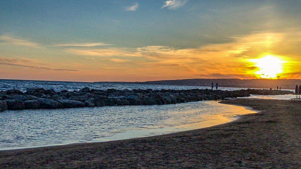 mare al tramonto con cielo rosso riflesso sull'acqua