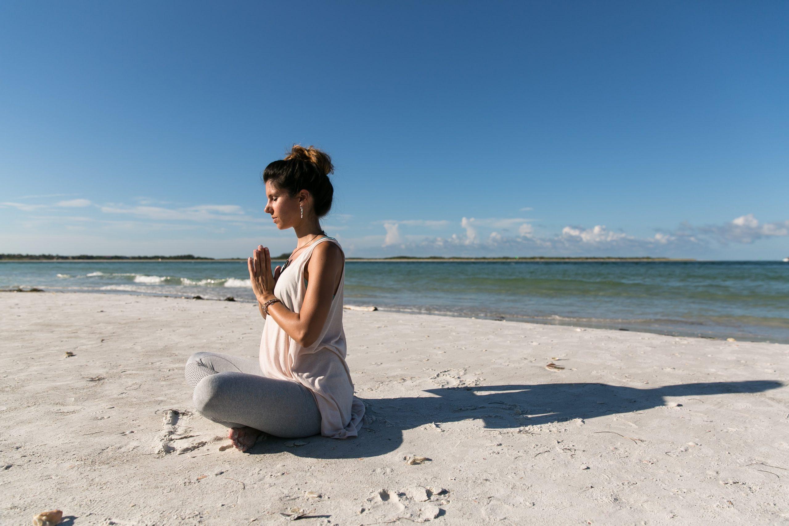 ragazza sulla spiaggia bianca con mani unite davanti al petto in meditazione