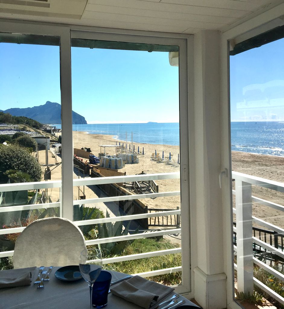 tavolo di un ristorante con vetrata vista mare e Monte Circeo