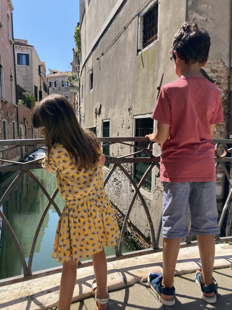 two kids looking at the canal from the top of a bridge in Venice