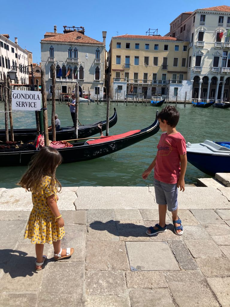 kids close to gran canal with gondolas behind them in a sunny day