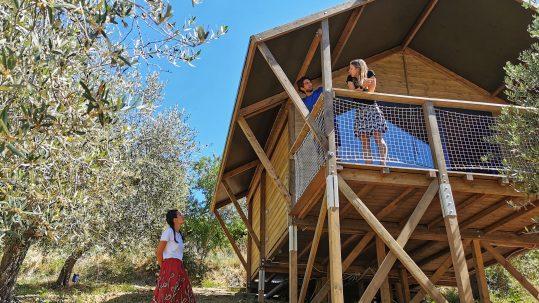 glamping in legno tra gli ulivi, due persone sul terrazzo e una donna con gonna rossa tra gli ulivi